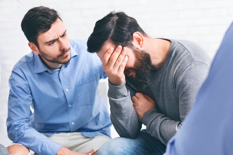 Patients comforting each other in men's rehab program