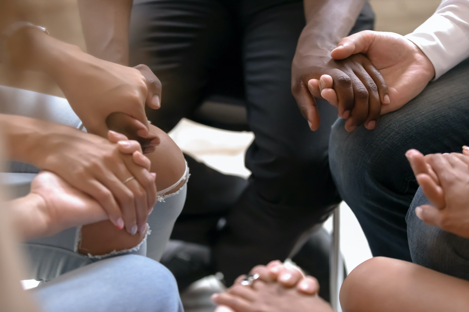 Group holding hands during recovery process for drug and alcohol addiction