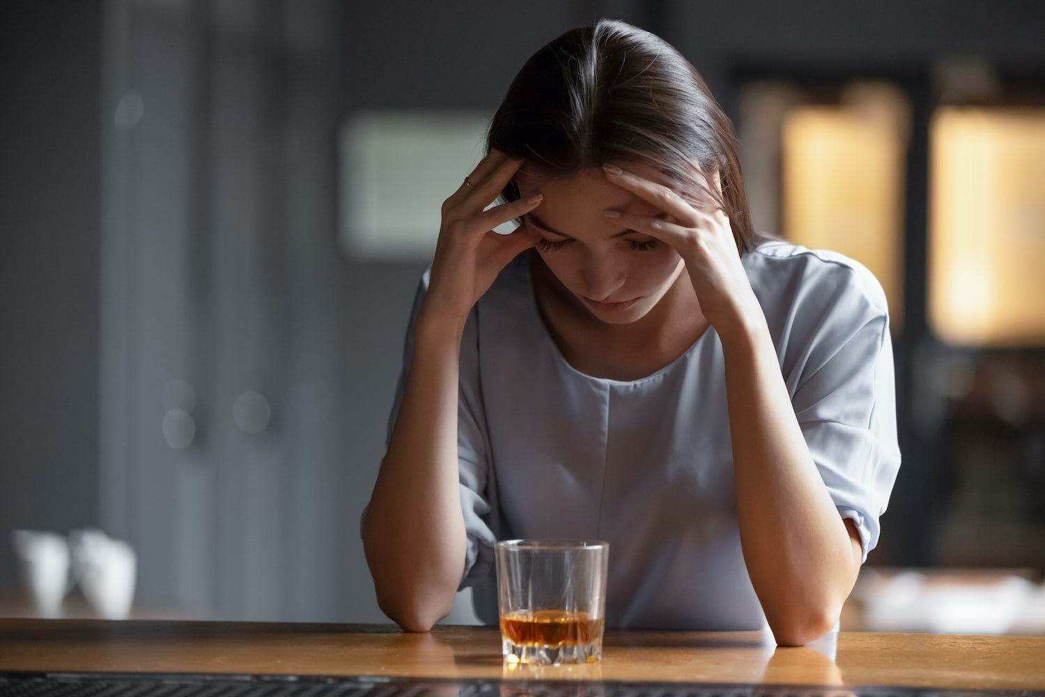 Woman at bar relapsing with alcohol