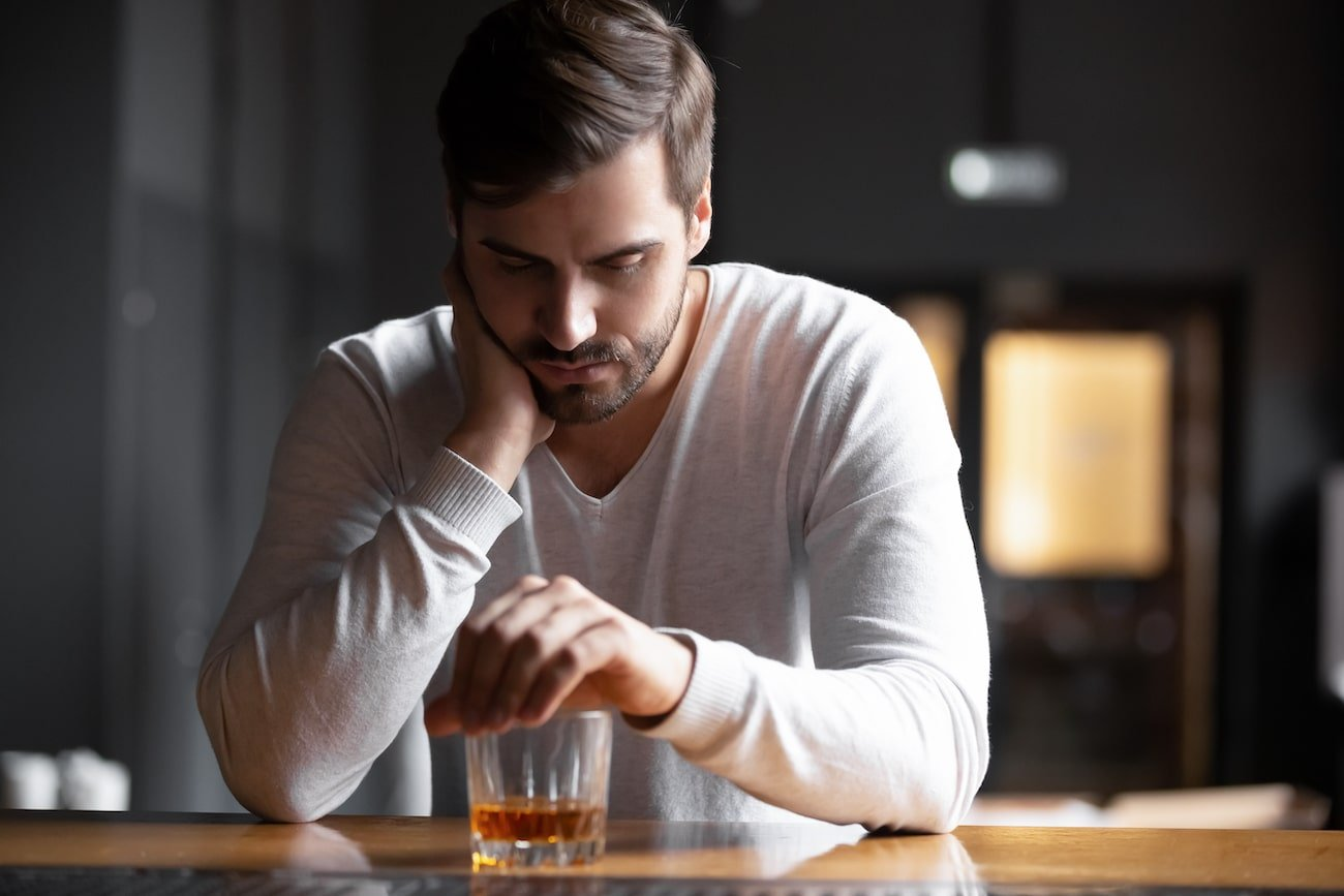 Alcoholic man looking sadly down at alcohol in a glass