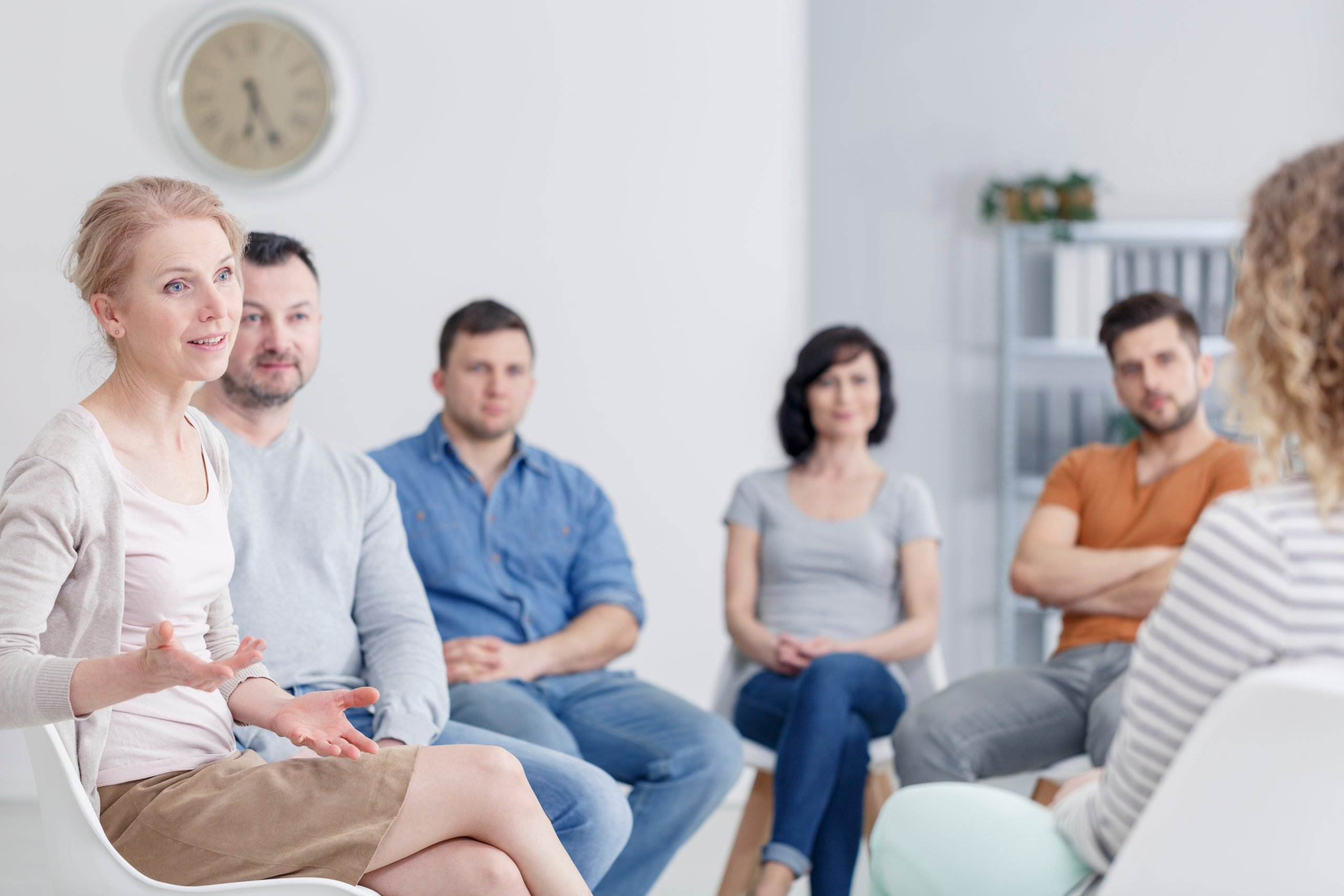 female speaking to her peers in an aa meeting
