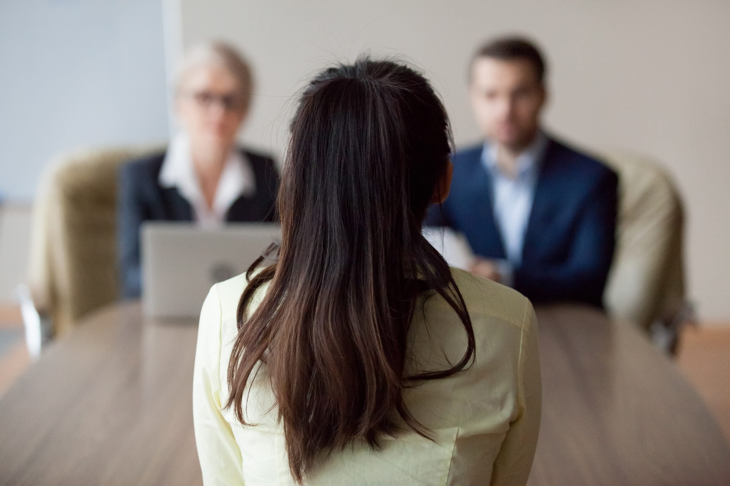 a woman with her back facing the camera in a job interview