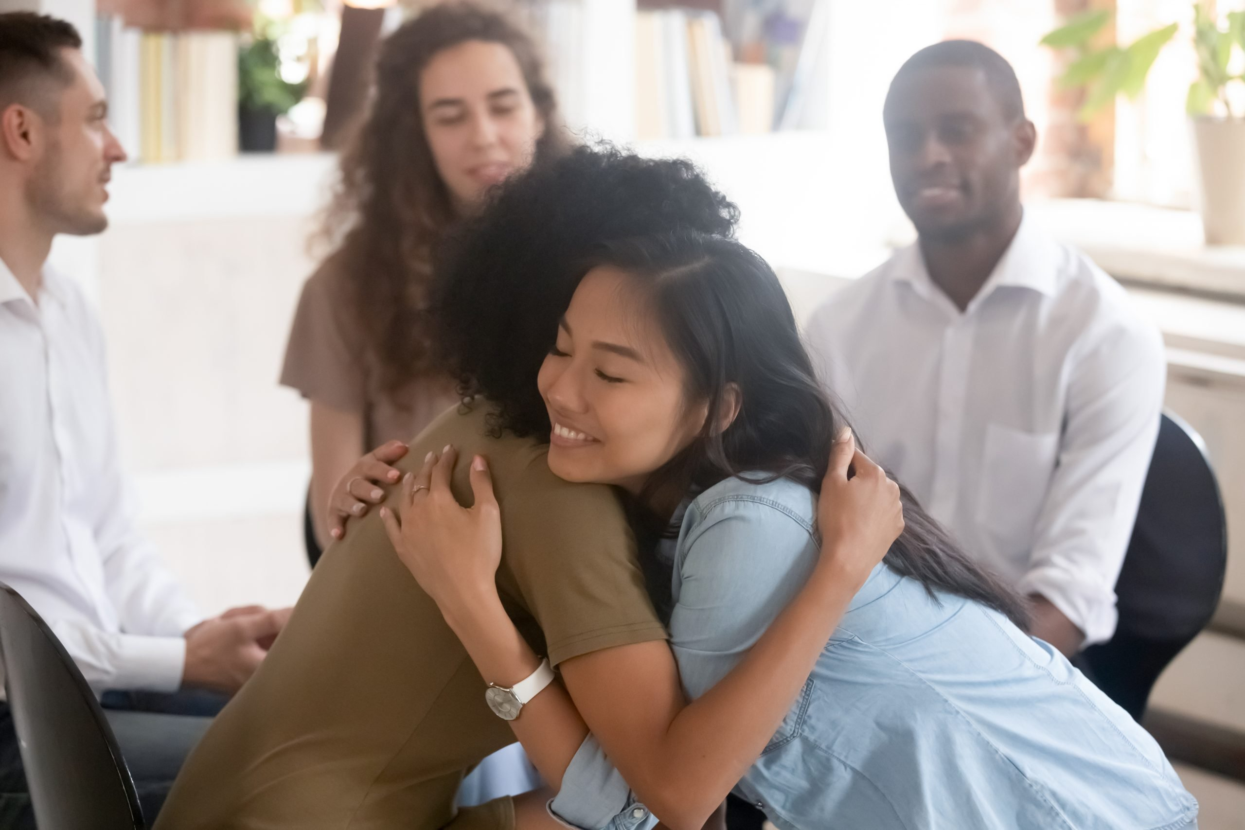 african american and asian women hugging each other for support at aa meeting