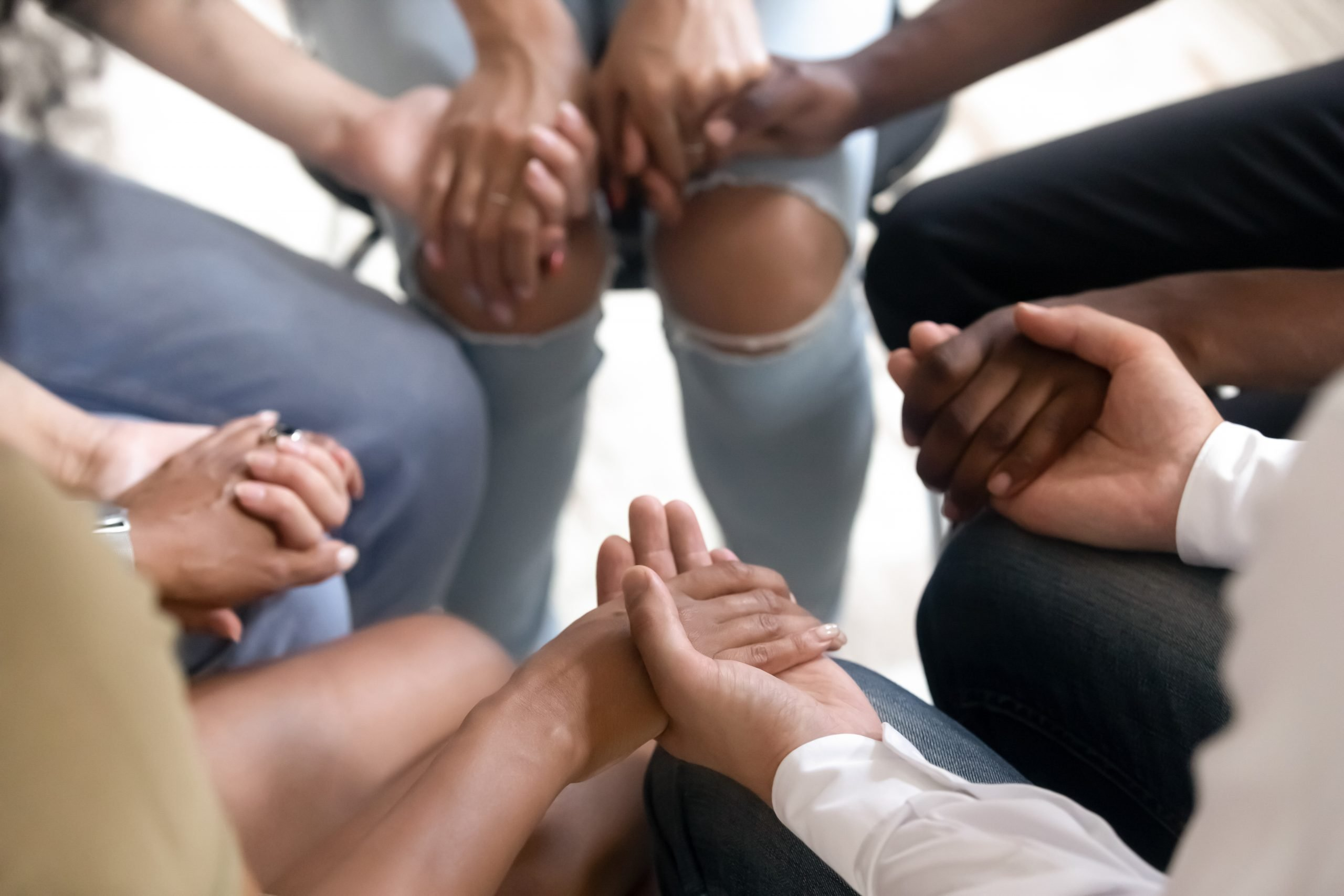 group of people sitting in a circle and holding hands